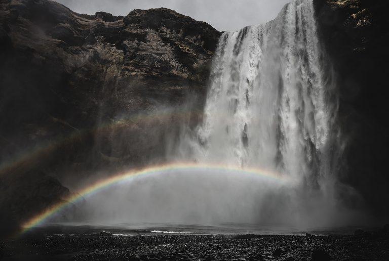 Momentaufnahme eines doppelten Regenbogens vor einem Wasserfall in Island