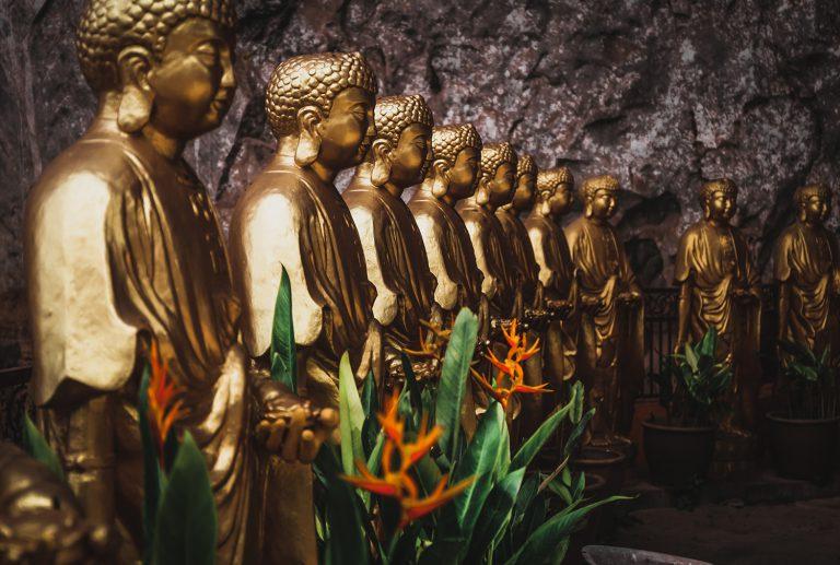 Foto mehrerer goldener Buddha-Statuen und dekorativer Pflanzen in einer Tempelanlage in Ipoh