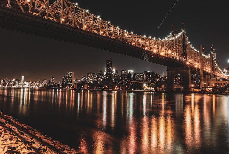 Panoramaaufnahme einer beleuchteten Brücke bei Nacht mit New Yorker Skyline im Hintergrund